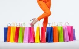 Jovem mulher em calças alaranjadas com sacos de compras Foto de Stock Royalty Free