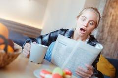 A jovem mulher em casa na leitura bebendo do chá da cozinha schoked pela notícia imagem de stock royalty free