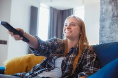 Jovem mulher em casa no canal de televisão do interruptor da sala de visitas fotos de stock