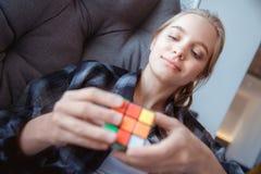 Jovem mulher em casa que encontra-se na rede que resolve o cubo do ` s do rubik imagem de stock royalty free