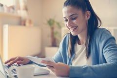Jovem mulher em casa que lê contas e que datilografa no portátil imagem de stock royalty free