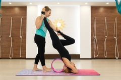 A jovem mulher em exercícios de uma ioga do sportswear com uma ioga roda dentro o gym Estilo de vida do esticão e do bem-estar fotos de stock