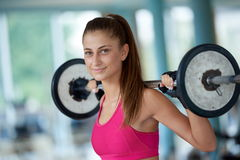 Jovem mulher em levantar peso do gym da aptidão Imagem de Stock