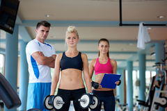 Jovem mulher em levantar peso do gym da aptidão Foto de Stock