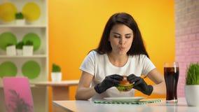 Jovem mulher em luvas de borracha pretas que come o Hamburger suculento que senta-se na tabela do café vídeos de arquivo