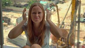A jovem mulher em seu apartamento sofre do ruído gerado pelo canteiro de obras fora da janela filme