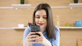 Jovem mulher em sua cozinha que datilografa no smartphone video estoque