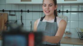 A jovem mulher em um avental do cinza grava o vídeo na cozinha clara filme