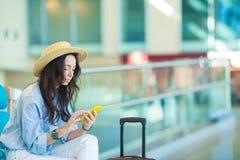 Jovem mulher em um avião de espera do voo da sala de estar do aeroporto Mulher caucasiano com o smartphone na sala de espera Foto de Stock Royalty Free