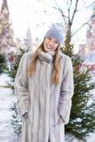 A jovem mulher em um azul fez malha o chapéu e o revestimento de vison cinzento fotografia de stock royalty free