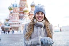 A jovem mulher em um azul fez malha o chapéu e o revestimento de vison cinzento fotos de stock royalty free