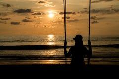 Jovem mulher em um balanço no por do sol fotografia de stock