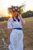 A jovem mulher em um branco longo bordou a camisa e em uma grinalda de Foto de Stock Royalty Free