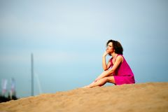 A jovem mulher em um cabelo encaracolado da American National Standard do vestido vermelho senta-se na areia Imagem de Stock Royalty Free