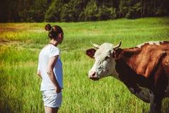 jovem mulher em um campo cercado por vacas Foto de Stock Royalty Free