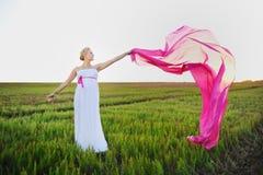 Jovem mulher em um campo verde Imagens de Stock