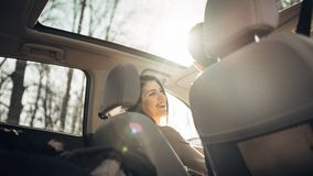 Jovem mulher em um carro, motorista fêmea que olha o passageiro e o sorriso Apreciando o passeio, viajando, conceito da viagem po foto de stock royalty free