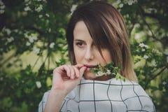 Jovem mulher em um dressstay quadriculado perto de uma ?rvore de floresc?ncia foto de stock