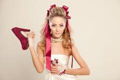 Jovem mulher em um estilo da boneca com as curvas vermelhas, guardando um vermelho alto-ele fotos de stock