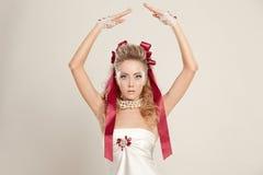 Jovem mulher em um estilo da boneca com as curvas vermelhas, mantendo suas mãos imagem de stock royalty free