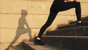 Jovem mulher em um fato de esporte preto que dobra os músculos da coxa interna no treinamento A menina estica os músculos do pé