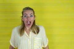 Jovem mulher em um fundo amarelo com expressão da surpresa e a cara entusiasmado fotografia de stock royalty free