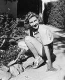 Jovem mulher em um jardim que faz a jardinagem (todas as pessoas descritas não são umas vivas mais longo e nenhuma propriedade ex Fotos de Stock Royalty Free