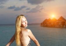 A jovem mulher em um maiô no por do sol no fundo do mar e das silhuetas das casas sobre a água fotos de stock