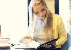 Jovem mulher em um restaurante que lê o menu fotografia de stock royalty free