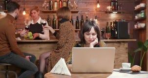 Jovem mulher em um restaurante que lê um texto em seu portátil video estoque