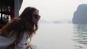 A jovem mulher em um revestimento branco e os ?culos de sol est?o olhando a vista bonita da ba?a ao sentar-se no barco filme