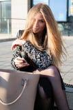 A jovem mulher em um revestimento na moda está sentando-se no parapeito de pedra na cidade Fotografia de Stock Royalty Free