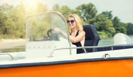 Jovem mulher em um roupa de banho que conduz um barco de motor imagem de stock