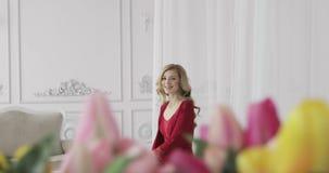 Jovem mulher em um roupa interior vermelho que senta-se na cama vídeos de arquivo