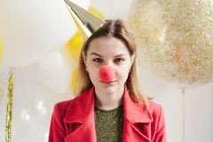 Jovem mulher em um tampão comemorativo que engana ao redor em um partido no fundo do balão Imagens de Stock Royalty Free