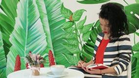 A jovem mulher em um terno listrado toma notas com um lápis em um bloco de notas vermelho imagem de stock royalty free