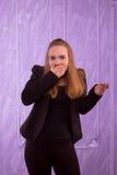 A jovem mulher em um terno preto cobriu sua boca com sua mão Imagens de Stock Royalty Free