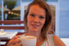 A jovem mulher em um terraço do café no verão aprecia um café Fotos de Stock Royalty Free