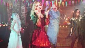 Jovem mulher em um traje do Dia das Bruxas da encantadora do vampiro que tenta seduzir filme