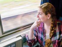 Jovem mulher em um trem que olha para fora a janela Foto de Stock