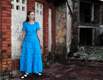 a jovem mulher em um vestido azul longo está perto da parede de pedra destruída velha da construção Fotografia de Stock Royalty Free