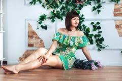 A jovem mulher em um vestido brilhante senta-se no assoalho em um fundo das flores Foto de Stock