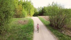 A jovem mulher em um vestido monta uma bicicleta na estrada no verão filme