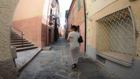 Jovem mulher em um vestido que anda nas ruas da cidade de Collioure nos Pyrenees orientais, França filme