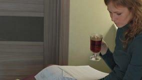 Jovem mulher em um vestido verde que senta-se no sofá com um portátil, funcionamento, estudando documentos, chá das bebidas, trab video estoque