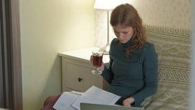Jovem mulher em um vestido verde que senta-se no sofá com um portátil, funcionamento, estudando documentos, chá das bebidas, trab filme