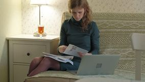 Jovem mulher em um vestido verde que senta-se no sofá com um portátil, funcionamento, estudando os documentos, trabalhando em cas video estoque