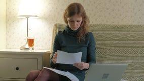 Jovem mulher em um vestido verde que senta-se no sofá com um portátil, funcionamento, estudando os documentos, trabalhando em cas vídeos de arquivo