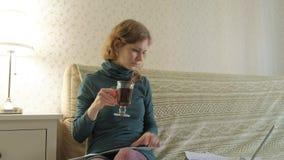 Jovem mulher em um vestido verde que senta-se no sofá com um portátil, usando o telefone, funcionamento, estudando documentos, be video estoque