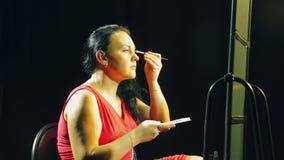 A jovem mulher em um vestido vermelho na frente de um espelho com uma escova põe a sombra sobre as pálpebras filme